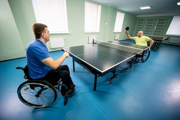 Взрослые мужчины-инвалиды в инвалидной коляске, играя в настольный теннис