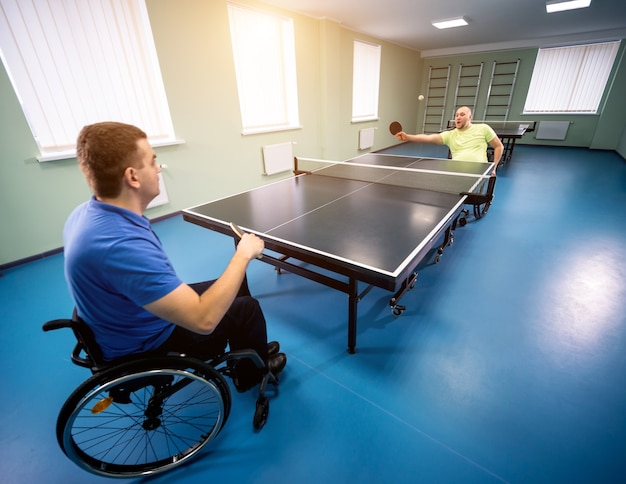 Adult disabled men in a wheelchair playing table tennis