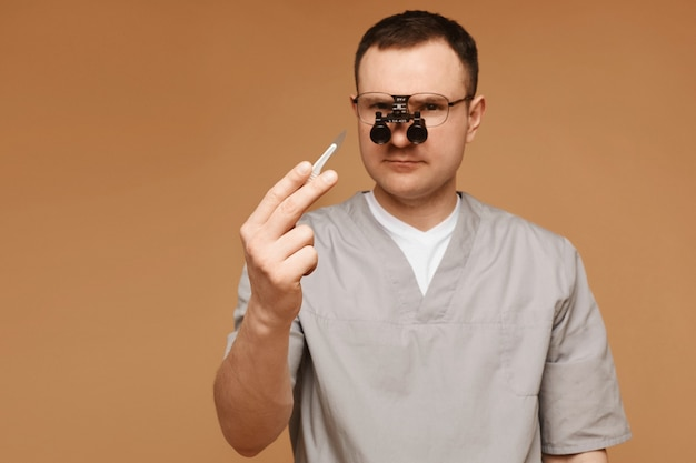 Adult doctor or surgeon man in magnification glasses posing with a scalpel