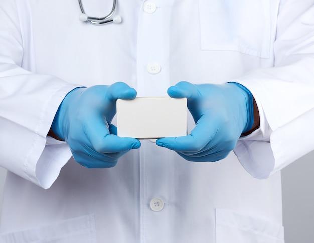 Взрослый врач-терапевт одет в белую форму халата, а синие стерильные перчатки стоят и держат стопку пустых визиток из белой бумаги