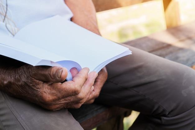 Обучение взрослых концепция обучения: счастливый азиатский пожилой мужчина-пенсионер сидит и читает книгу в саду дома на открытом воздухе для обучения или расслабления самостоятельно