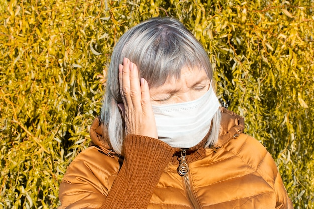 Взрослая пожилая грустная старшая женщина в медицинской защитной маске держит голову, больное ухо, средний отит осенью на улице