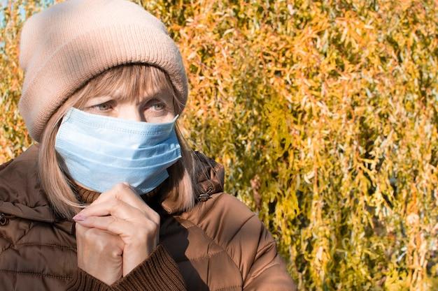 Взрослая пожилая грустная старшая женщина в медицинской защитной маске молится богу осенью на улице