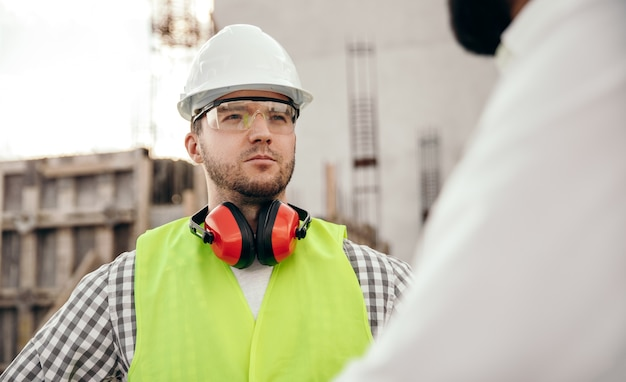 Взрослый инженер, стоящий с коллегой на строительной площадке