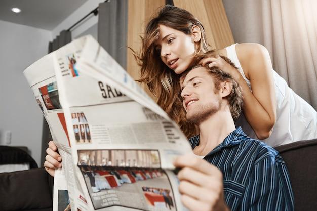 Взрослые европейские пары сидя в живущей комнате, читая газету в утре все еще нося пижаму. муж позвонил жене, чтобы проверить интересную статью о своей компании