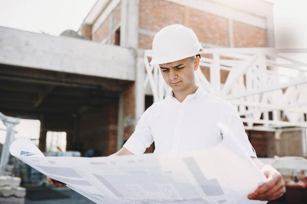 성인 유럽 남성 마스터 건설에있는 건물의 계획을 심각 하 게보고.