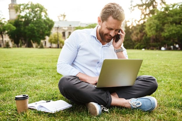 Adult european man in business clothing, sitting on grass in park with legs crossed and having business call while working on silver laptop