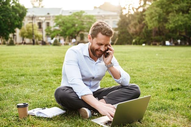 비즈니스 의류에 성인 유럽 남자, 다리를 건너 공원에서 잔디에 앉아 실버 노트북에서 작업하는 동안 휴대 전화로 말하기