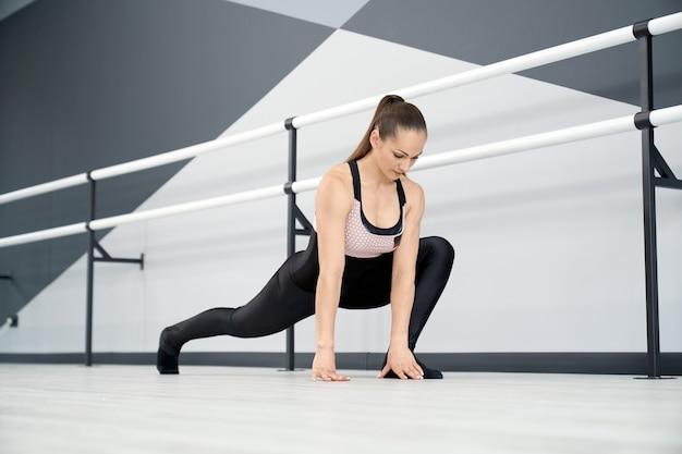 Adult female athlete stretching legs in ballet studio