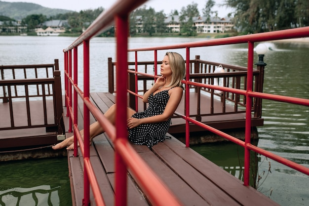 Adult female in a black dress sitting on the pier and enjoys relaxing