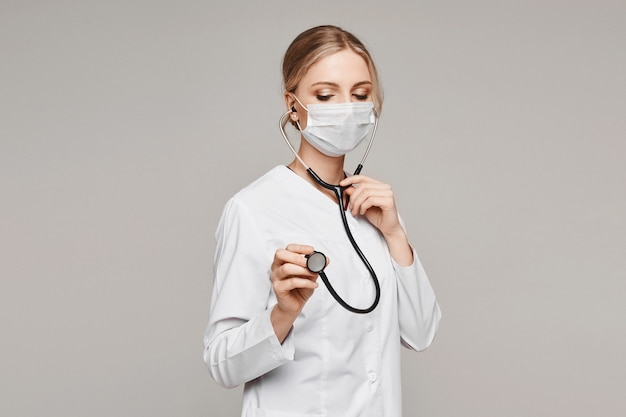 Взрослая женщина-врач в медицинской форме и защитном лице, закрывающем лицо, позирует со стетоскопом на сером