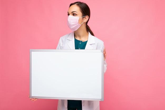 空の白い磁気ボードを保持している保護フェイスマスクと白い医療コートの大人の女性医師