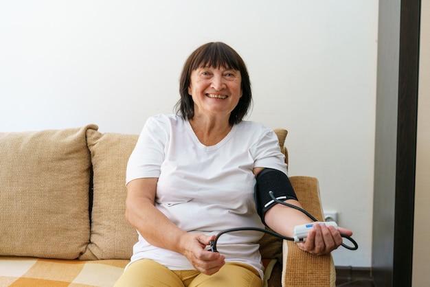 전자 기기로 혈압과 맥박을 측정하는 성인 여성