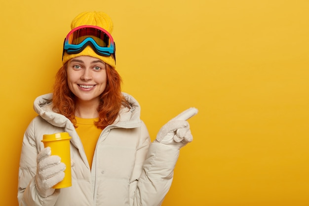 Adult female snowboarder with ginger hair, enjoys hot bevergae during winter time, wears ski clothing, points away on free space for your promotional content or text.