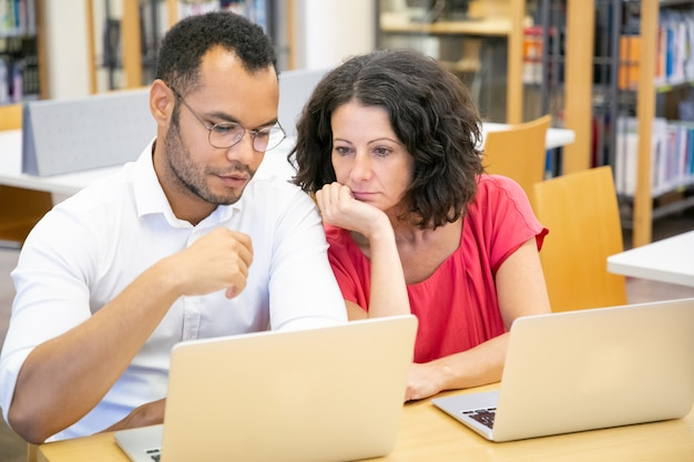 Adult female student consulting monitor of college mate
