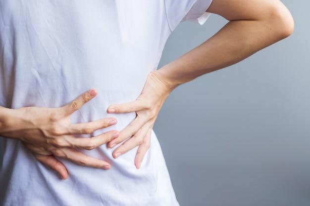 灰色の背景に筋肉痛のある成人女性。梨状筋症候群、腰痛、脊髄圧迫による背中の体の痛みを抱える年配の女性。スポーツ傷害と医療概念