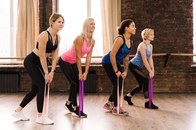 Взрослые женщины тренируются вместе в тренажерном зале