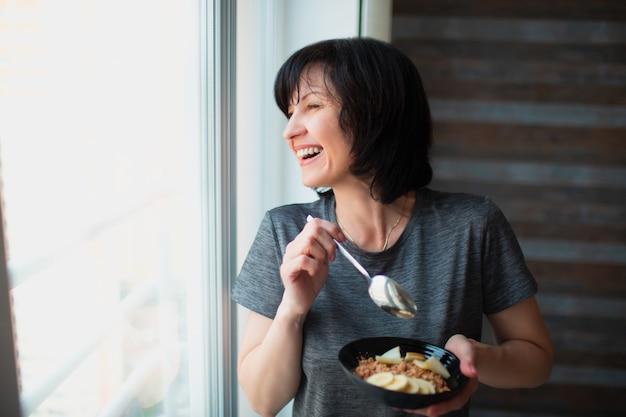 大人は、家で朝食を食べるスリムな女性に合います。健康とウェルネスに注意してください。ボウルに朝食の食事を持っているシニアの女性。ウィンドウを見てください。