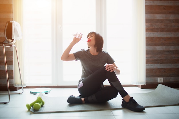Adult fit slim woman has workout at home. senior model drinking water sitting on yoga mat during exercise break. hydration balance. exercising for well shaped body. take care of herself.