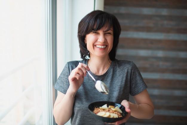 大人は朝食だけでスリムな女性に合います。ボウルを手にして陽気な笑顔。シニアのしっかりした造りの人は彼女の健康を世話します。