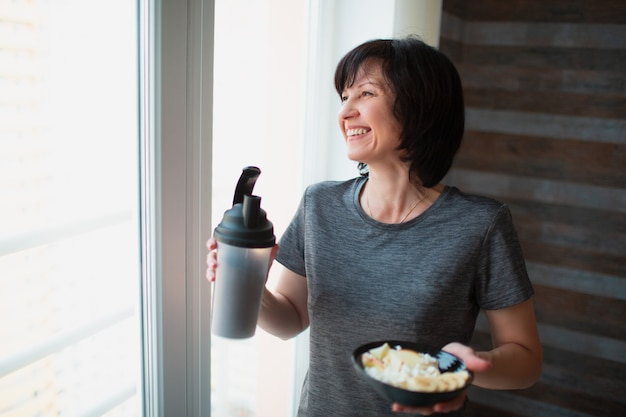Adult fit slim woman posing on camera. holding bowl and bottle in hands. eating meal after training or exercise. enjoying food alone in room.