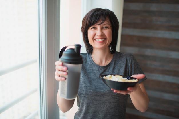 大人は、スリムな女性がカメラにポーズを合わせてください。ボトルとボウルを手に持って。カメラに微笑んでいます。トレーニング後の朝食時間の食事。健康で美しくいよう。 Premium写真