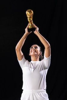 Adult fit woman raising soccer trophy