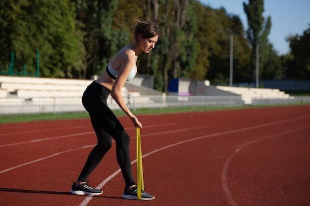 朝の屋外で輪ゴムでトレーニングをしている大人のフィットネス女性。空きスペース