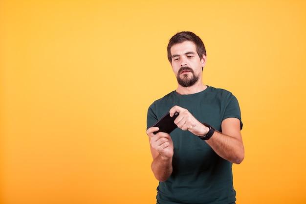 스튜디오의 노란색 배경에서 스마트폰으로 비디오 게임을 하는 성인 게이머. 레져 활동