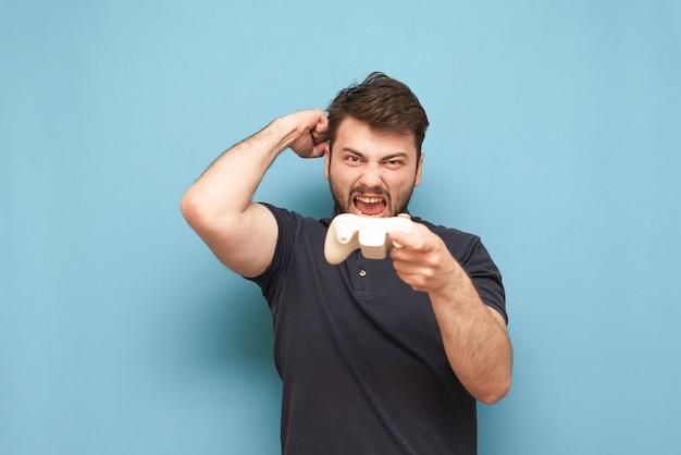 Взрослый геймер с бородой, держит в руках джойстик, эмоционально радуется победе в игре на синем