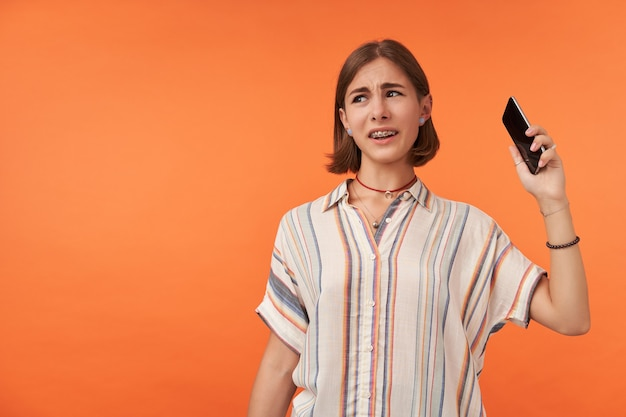 Adult girl looking unhappy and hanging up a phone. unlike call. student pick up a phone, wearing striped shirt, teeth braces and bracelets. watching to the left at copy space over orange wall