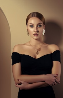 Adult girl wearing nature inspired golden jewelry set and black dress and leaning in beige room