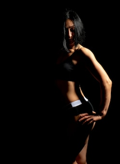 Adult girl with a sports figure in black bra and black shorts standing on dark