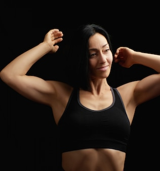 Adult girl with a sports figure in black bra standing on dark