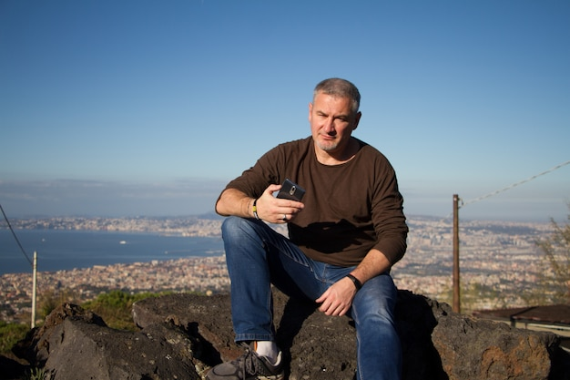 Adult gray-haired man with a beard sits on top of mount vesuvius with a view of naples at sunrise