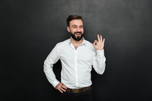 Adult guy in office posing on camera, smiling and gesturing with ok sign expressing everything is alright over dark gray