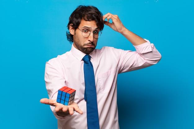 Adult handsome indian businessman solving a intelligence challenge