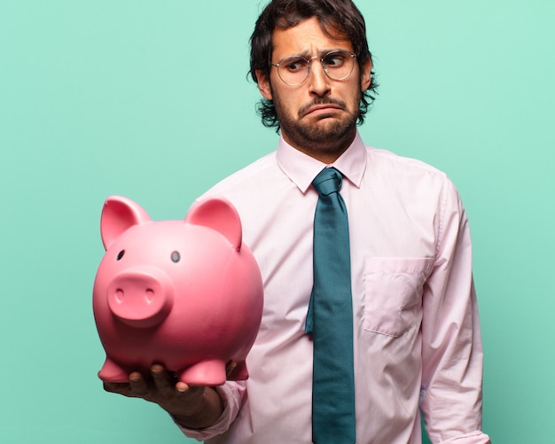 Adult handsome indian businessman with a piggy bank