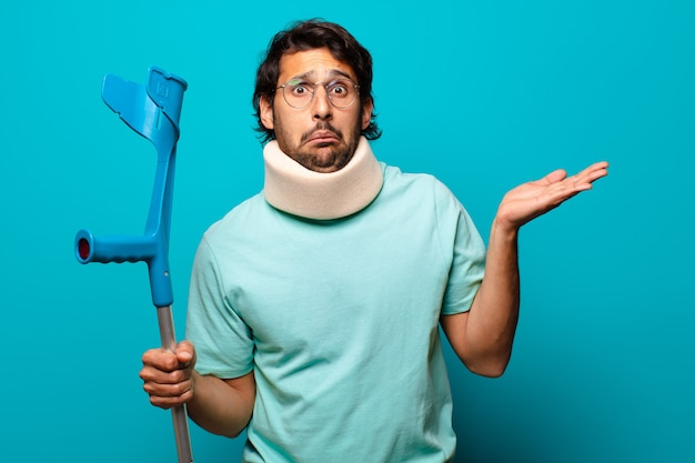 Adult handsome indian man who has suffered an accident.  crutch and collar concept