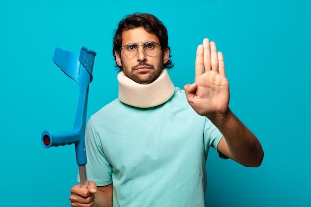 事故に見舞われた大人のハンサムなインド人。松葉杖と襟のコンセプト