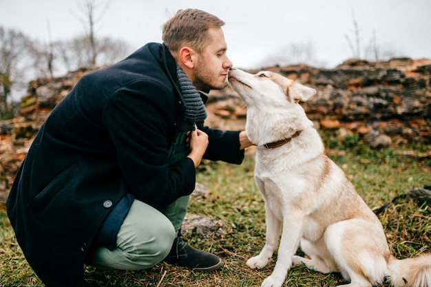 Adult handsome man in business clothes walking with cute lovely husky puppy dog outdoor beyond brick wall of european castle remains. male owner with furry purebred canine hugs. boy embracing his dog