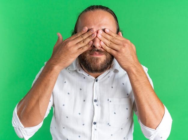 Uomo bello adulto che copre gli occhi con le mani isolate sul muro verde