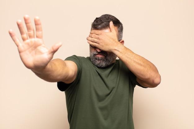 Взрослый красавец закрывает лицо рукой и поднимает другую руку вперед, чтобы остановить камеру, отказываясь от фотографий или изображений