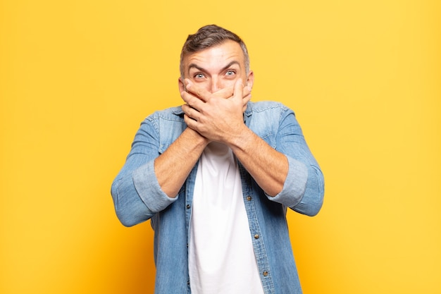 Adult handsome man covering mouth with hands with a shocked