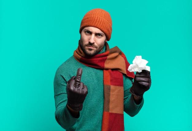 怒り、イライラ、反抗的、攻撃的な大人のハンサムな男は、中指をひっくり返し、反撃します。病気と寒さの概念