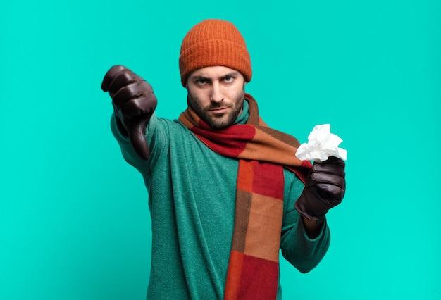 大人のハンサムな男は、真剣な表情で親指を下に見せて、十字架、怒り、イライラ、失望または不満を感じています。病気と寒さの概念