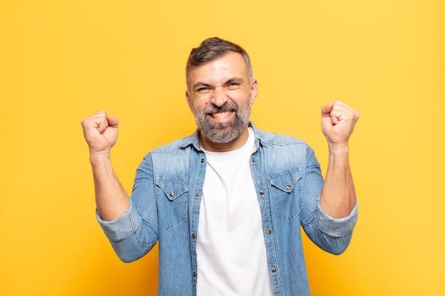 Взрослый красивый мужчина чувствует себя счастливым, позитивным и успешным, празднует победу, достижения или удачу