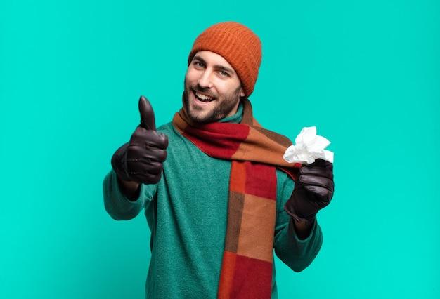 誇り高き、のんき、自信と幸せを感じ、親指を立てて前向きに笑っている大人のハンサムな男。病気と寒さの概念