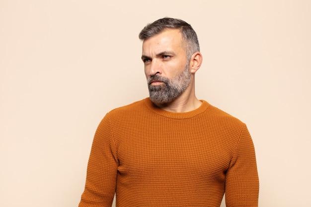 Взрослый красивый мужчина грустит, расстроен или зол, смотрит в сторону с негативным отношением и хмурится в знак несогласия.