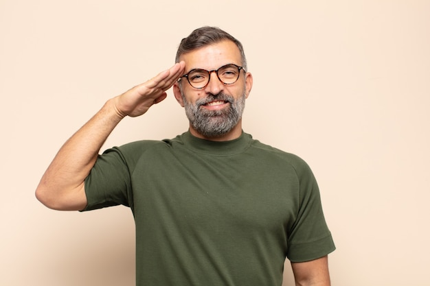 존경을 보여주는 명예와 애국심의 행위에 군사 인사로 인사하는 성인 잘 생긴 남자